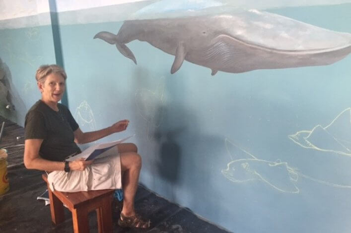 Artist and illustrator Carlyn Iverson, working on a mural in the Charles Darwin Exhibition Hall.