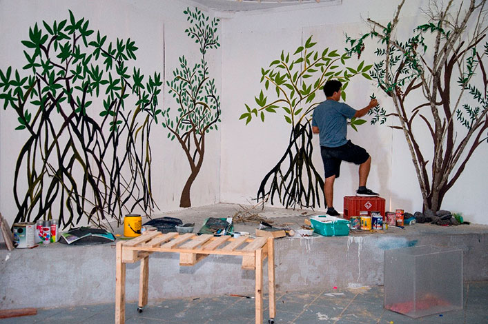 Jonathan Atiencia building a mangrove forest with recycled materials, rocks and lose branches.