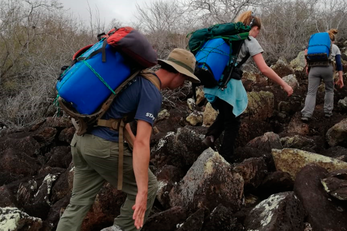 The team walking over the rocky terrain to the study site, with the 'chimbuzos' of water to fill the Groasis technology with