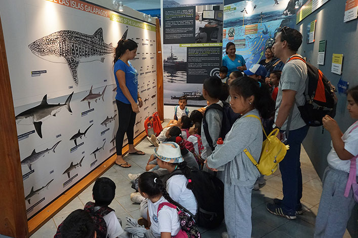 Daniela Vilema, leader of the marine education project, teaching students about the species of sharks present in Galapagos