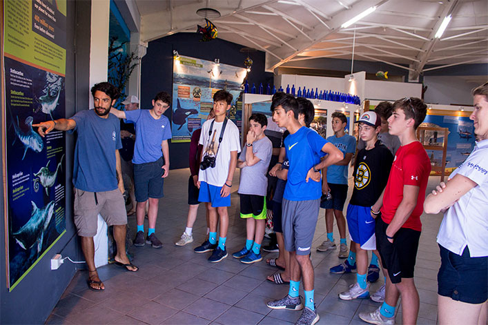 Students from the Fessenden School in Massachusetts visit the CDF's Marine World exhibit to learn about different shark species in Galapagos. Majority are wearing Blue Feet Foundations socks