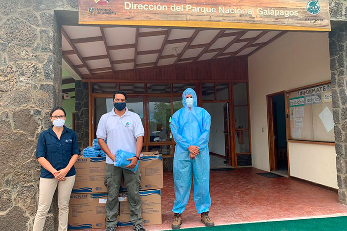 Johanna Carrión, representative of the Charles Darwin Foundation, handing over the protection suits to Danny Rueda, Director of the Galapagos National Park and Cristian Sevilla, Director of Ecosystems of the Galapagos National Park.