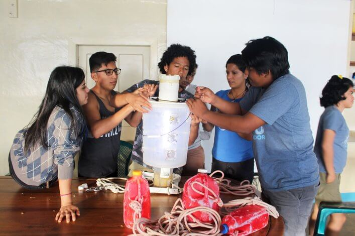 Students preparing light traps to catch fish larvae at the Research Station's beach.