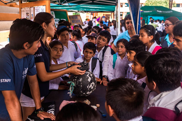 Wilson Íñiguez and Sofía Green explaining about the role of marine trash as an introduction vector for invasive species to students from a local school during an event for the International Day for Biological Diversity. Photo by Juan Manuel García.